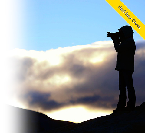 Mike Corrado photo of a photographer in silhouette against a blue sky