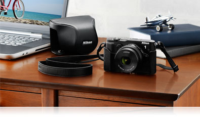 Photo of the Nikon 1 V3, its case, a laptop and accessories on a desk