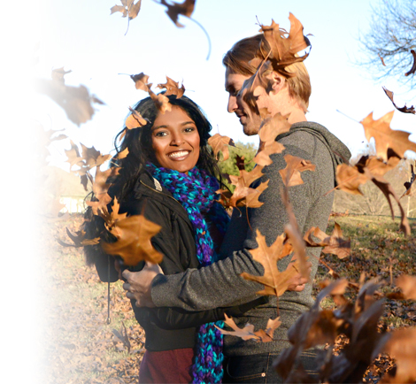 photo of a young couple in a field in fall with leaves in the air around them