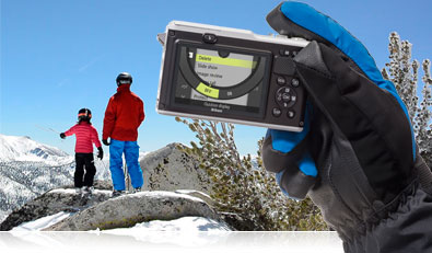 Photo of the Nikon 1 AW1 in a gloved hand with a parent and child in the background on a mountain