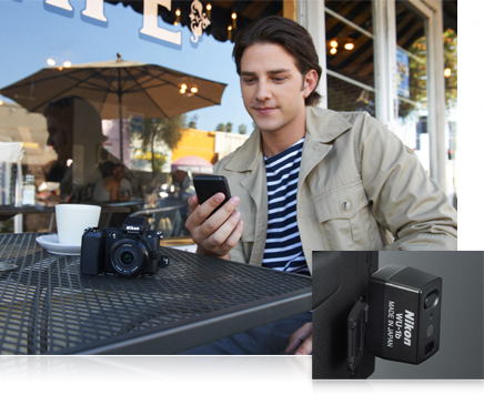 photo of a man at an outdoor cafe holding a smartphone and a close up shot of the WU-1b device in the Nikon 1 V2
