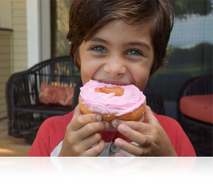1 NIKKOR VR 10-30mm f/3.5-5.6 PD-ZOOM lens photo of a kid eating a donut