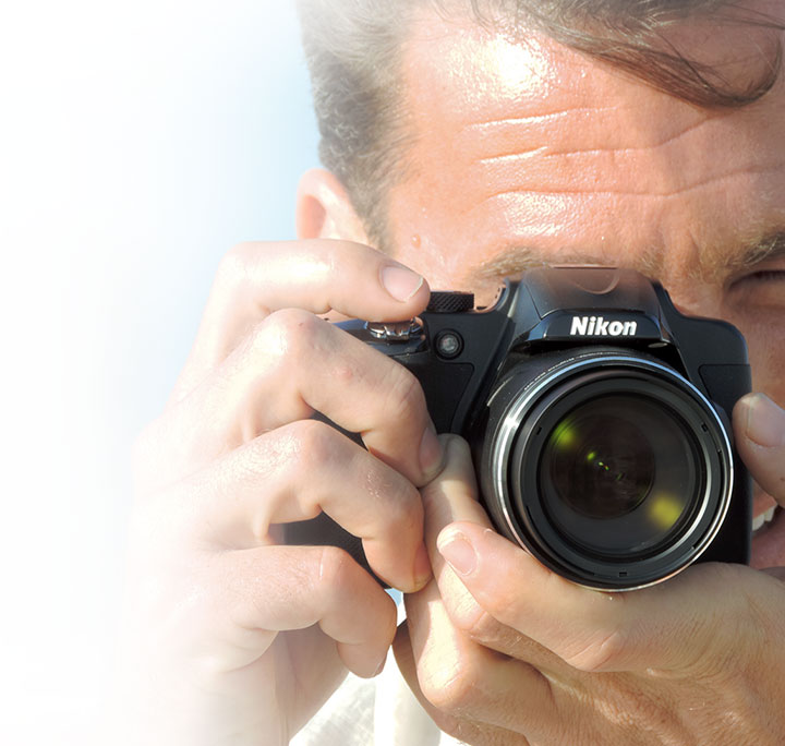 Photo of a man holding the COOLPIX P600 up to his eye, shooting