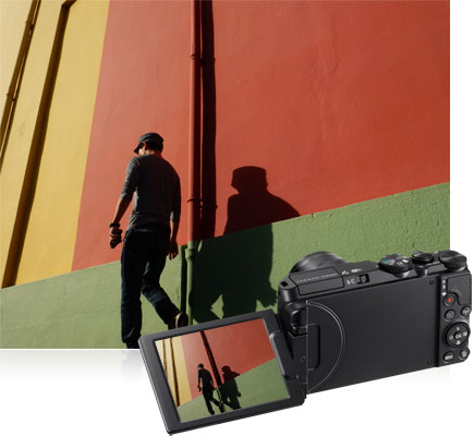 COOLPIX S9900 photo of a man walking next to a colorful wall, inset with the image on the LCD of the camera