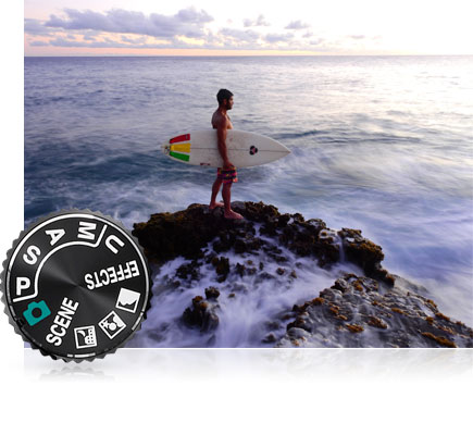 COOLPIX P900 photo of a surfer on the jetties at the water's edge and the mode dial inset