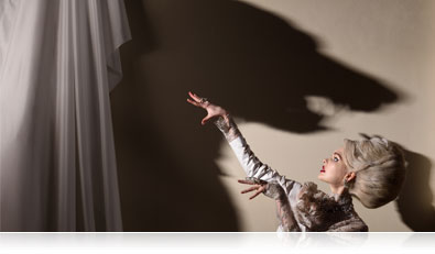 Photo of a model with a shadow of a wolf on the wall showing creativity