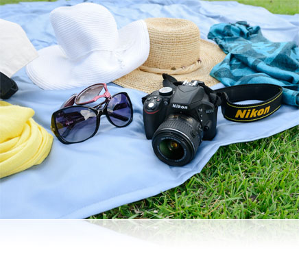 Photo of the Nikon D3300 and hats, scarf and sunglasses on a blanket on the grass