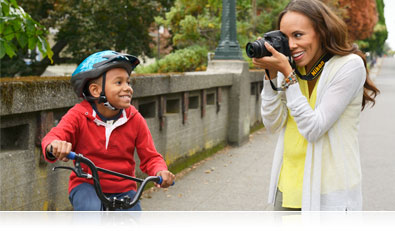 D3300 photo of a woman photographing her son on a bicycle