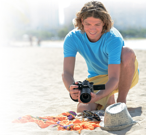 photo of a young man at the beach, shooting objects on a towel