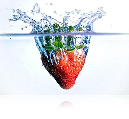 Fotografia de um morango caindo e espirrando água, feita usando a lente AF-S DX NIKKOR 18-105mm f/3.5-5.6G ED VR
