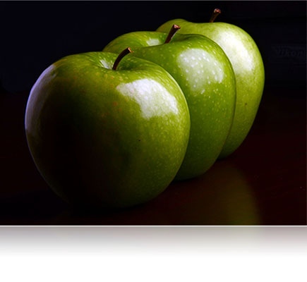Fotografia de três maçãs verdes feita com a lente AF-S DX NIKKOR 18-105mm f/3.5-5.6G ED VR