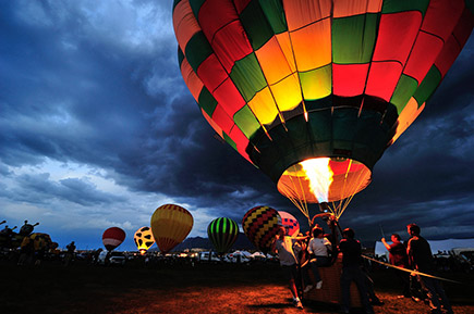 Photo of a hot air balloon with people standing around it in the foreground in low light