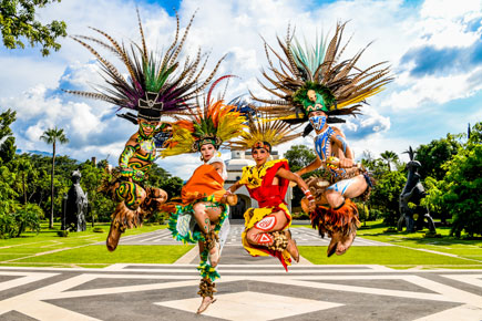 Ben Olivares photo of dancers in colorful costumes, jumping in air