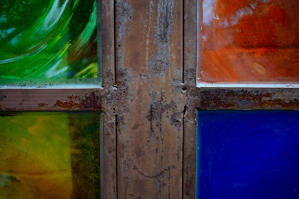 Photo of a painted window, with each pane another color: red, blue, yellow and green.