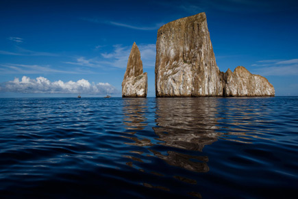 Photo of towers of rock jutting out of the water with their reflection