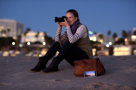Photo of a woman taking a photo while her smartphone sits nearby, with an image on the LCD