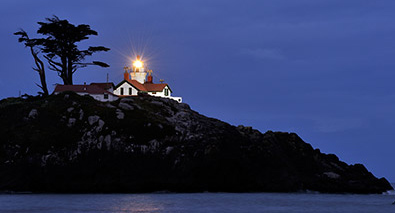 Photo of a lighthouse on a hill, in low light at night