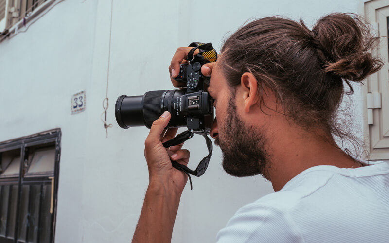 photo of a man with a camera and NIKKOR Z DX 18-140mm f/3.5-6.3 VR lens