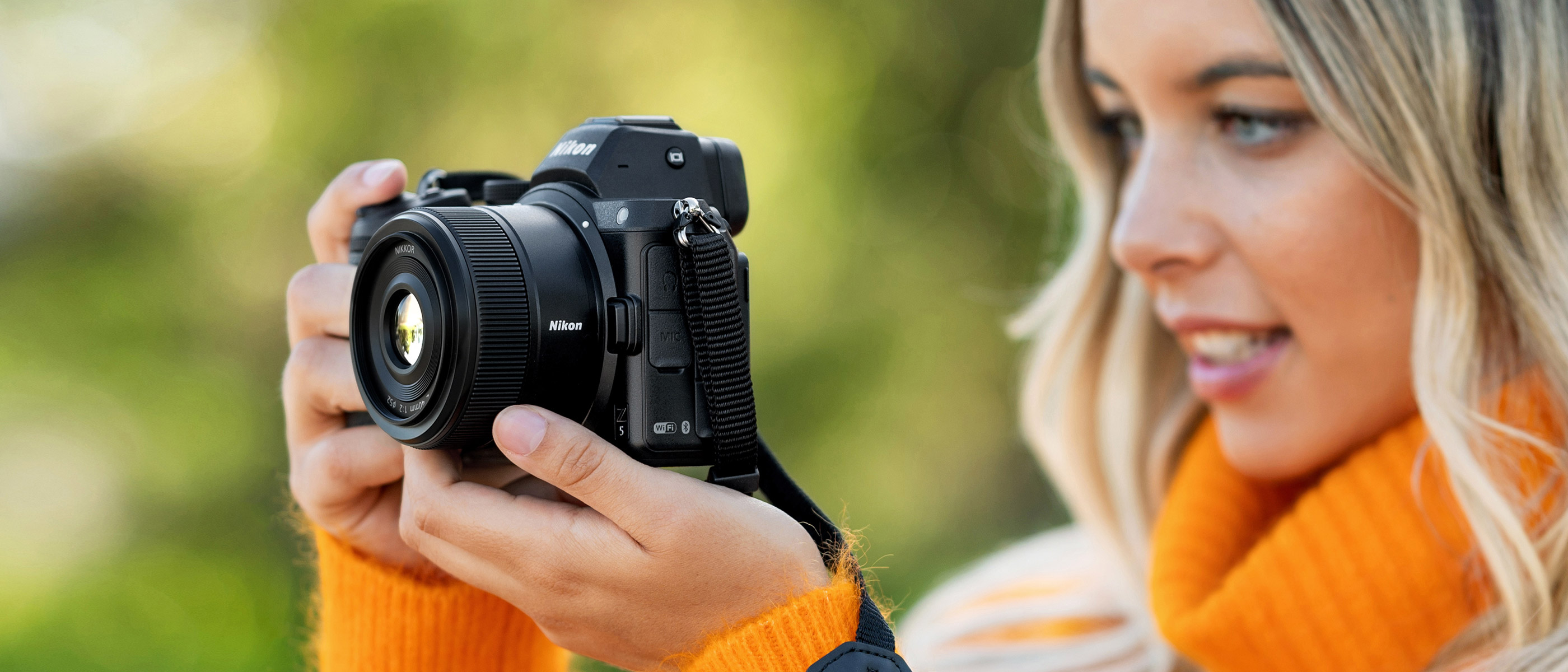 photo of a woman holding a camera with the NIKKOR Z 40mm f/2 lens attached