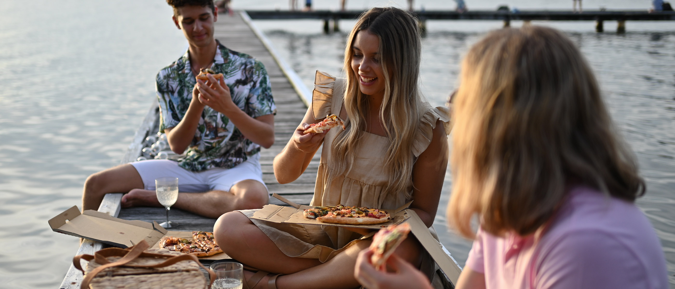 photo of people eating pizza on a dock, over water, taken with the NIKKOR Z 40mm f/2