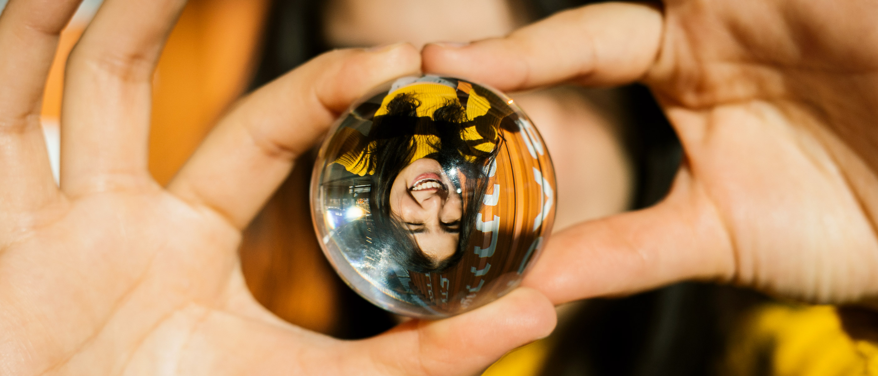 photo of a girl holding a lens ball with her portrait upside down inside the ball, taken with the NIKKOR Z 40mm f/2