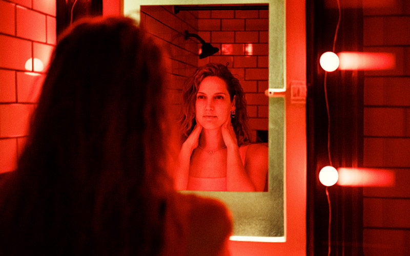 photo of a woman looking in the mirror, with red gel lighting, taken with the NIKKOR Z 40mm f/2