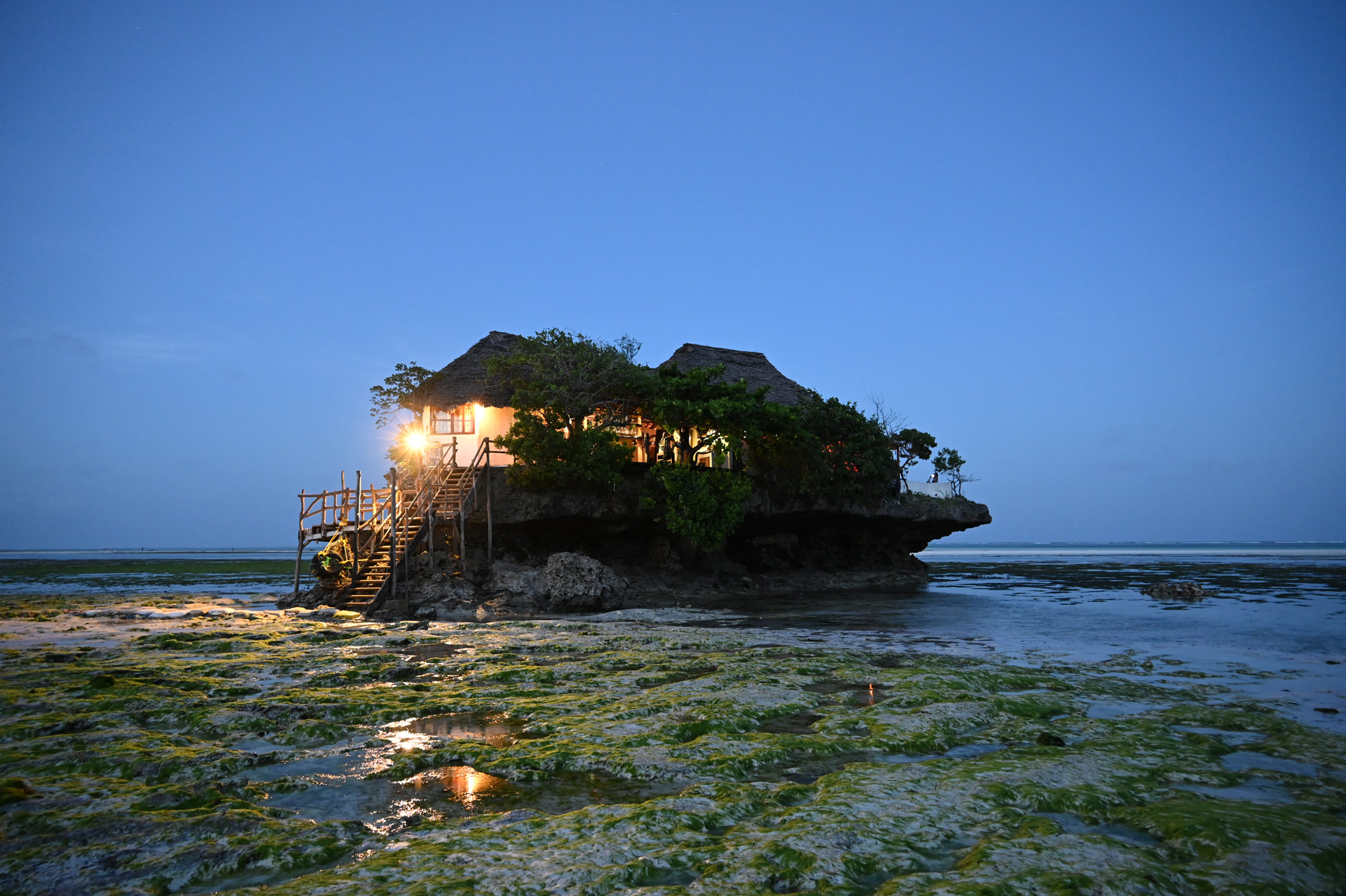 Low light photo of a house built on rocks at the shore, taken with NIKKOR Z 24-200mm f/4-6.3 VR