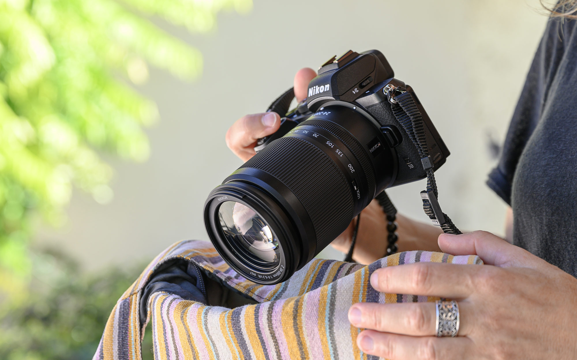 Photo of a woman's hands holding a Z 50 camera with the NIKKOR Z 24-200mm f/4-6.3 VR lens attached.
