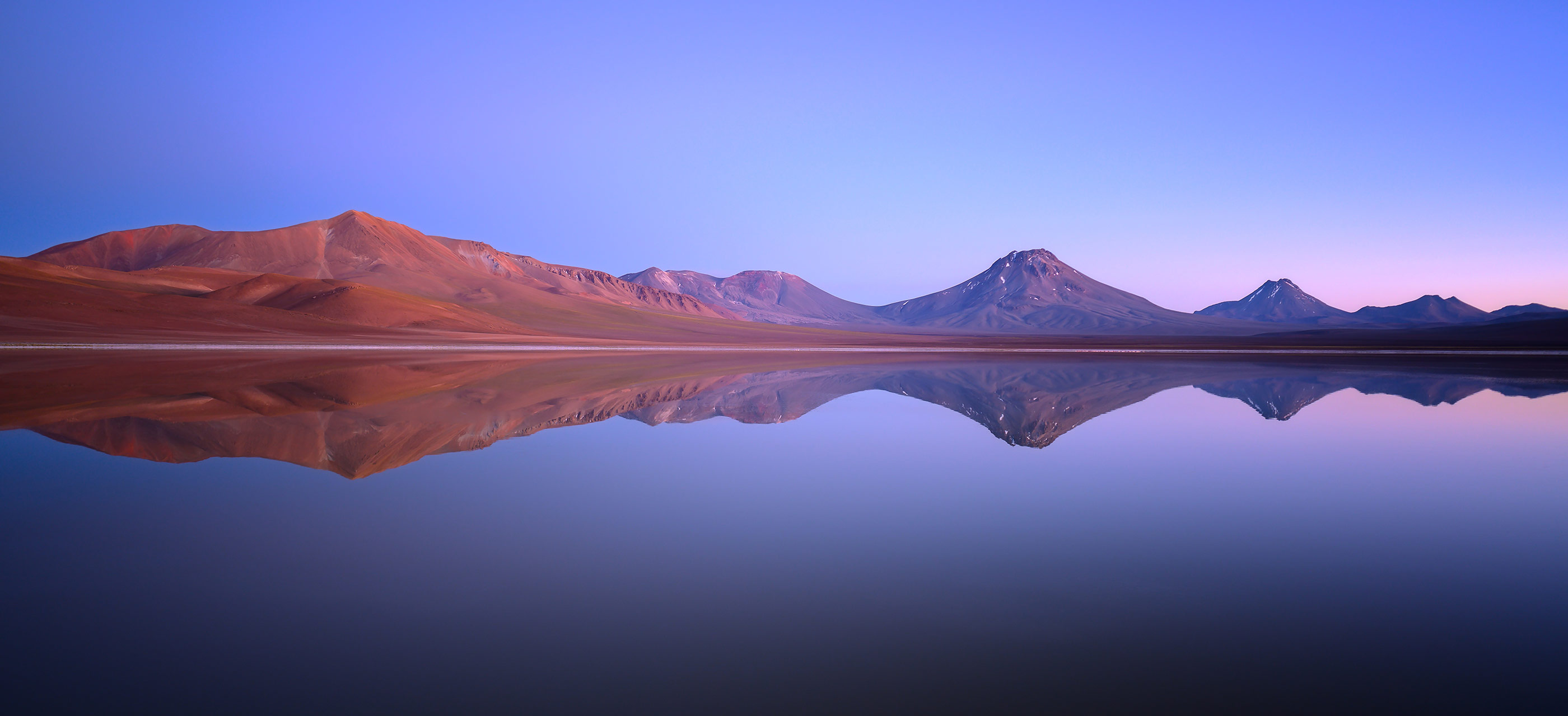 Landscape photo of hills and their reflection in water, taken with the NIKKOR Z 20mm f/1.8 S