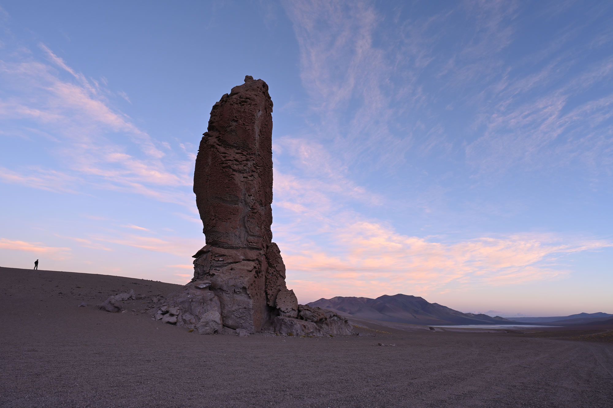 Photo of a rock outcropping in the desert, with a figure in silhouette in the distance, taken with the NIKKOR Z 20mm f/1.8 S