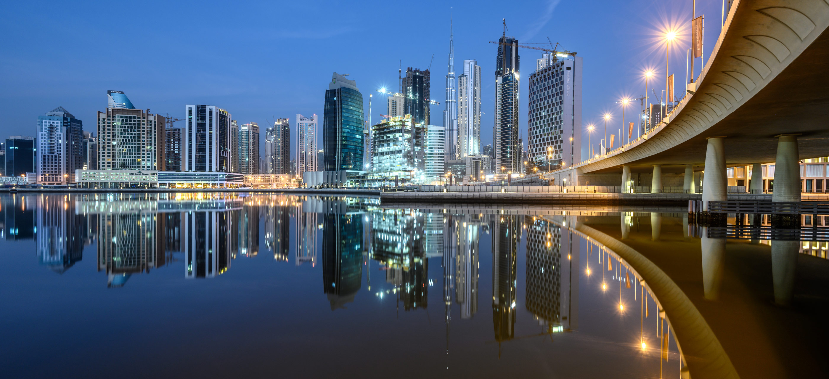 Low light image of a city and its reflection in water, captured with the NIKKOR Z 14-30mm f/4 S lens