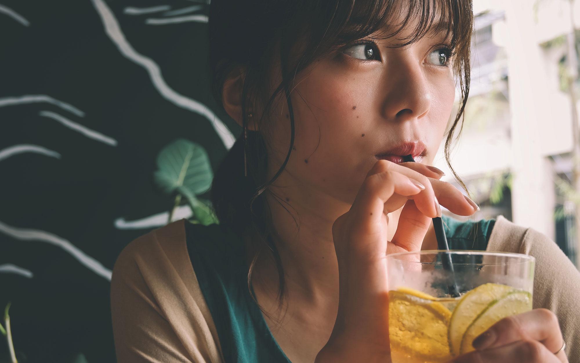 Z 50 ve NIKKOR Z DX 16-50mm f / 3.5-6.3 VR lens ile çekilmiş, bardağın içinden kamışla içen bir kadının fotoğrafı