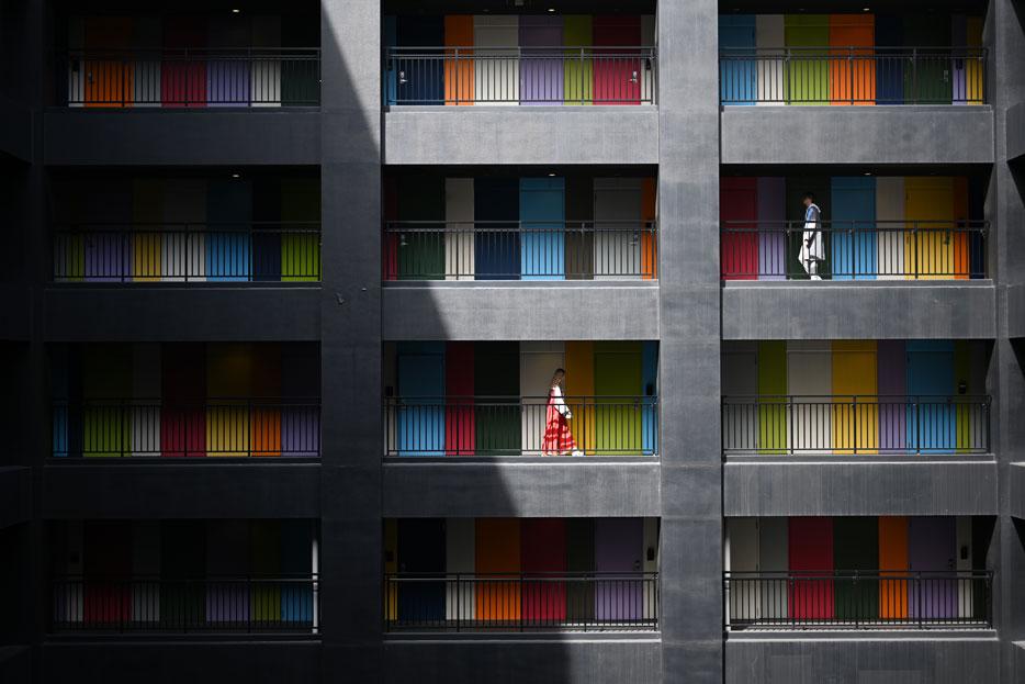 Z 7 ve NIKKOR Z 50mm f / 1.8 S lens ile çekilen, farklı seviyelerde yürüyen iki insanla dört katlı bir binanın balkonlarının fotoğrafı