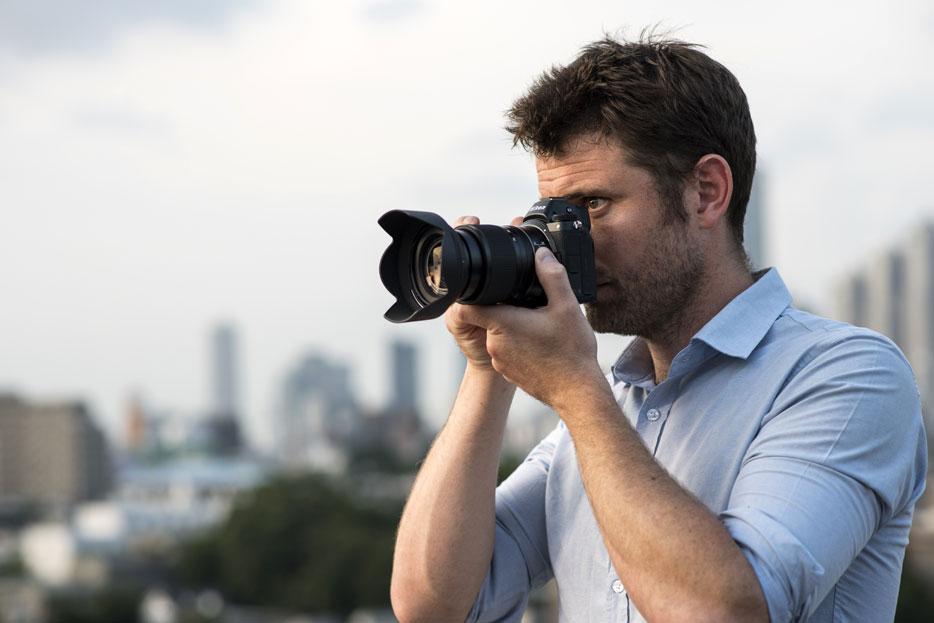 Z 7 ve NIKKOR Z 24-70mm f / 4 S lensini tutan bir adamın fotoğrafı