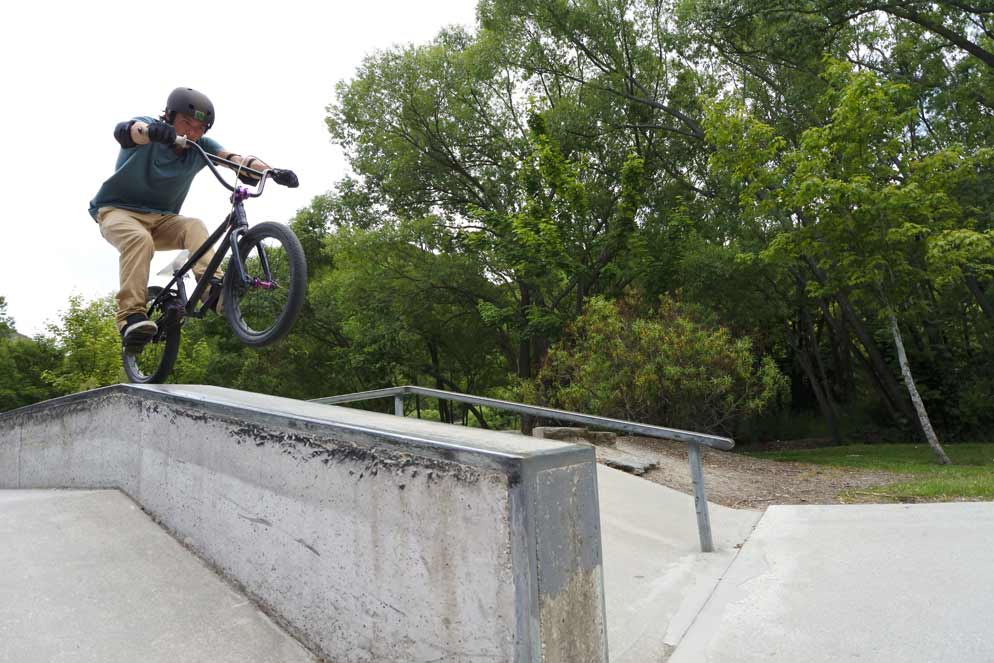 Nikon 1 J5 20 frames per second continuous shooting photo of a boy riding a bike on a railing doing stunts