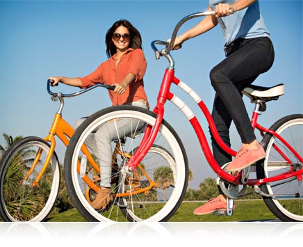 photo of two women on bicycles