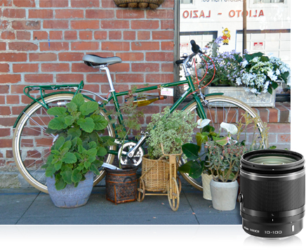 photo of bicycle against brick wall with plants surrounding it and product shot of the 1 NIKKOR 10-100mm lens