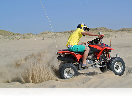 photo of a man on a red 4 wheel ATV on the beach