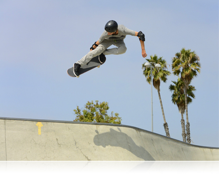 photo of a skateboarder catching air above a concrete pool or bowl