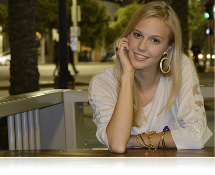 photo of a young woman leaning on a table wearing a white top and gold jewelry