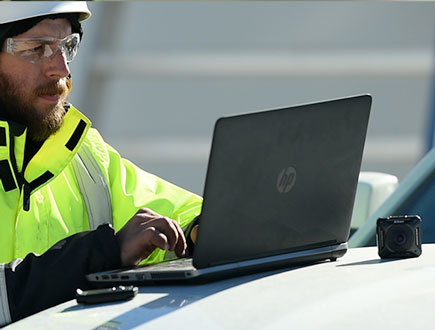 Man with hard hat and yellow jacket along with laptop computer and KeyMission 360 camera on location