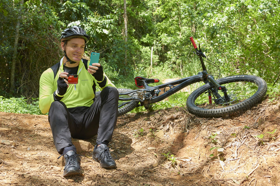 Photo of a mountain biker holding the W300 and a smartphone