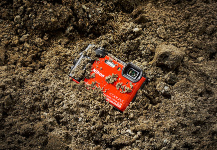 Photo of the COOLPIX W300 half buried in dirt