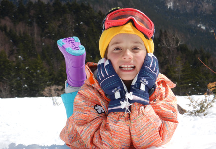 Photo of a kid on the snow smiling at the camera