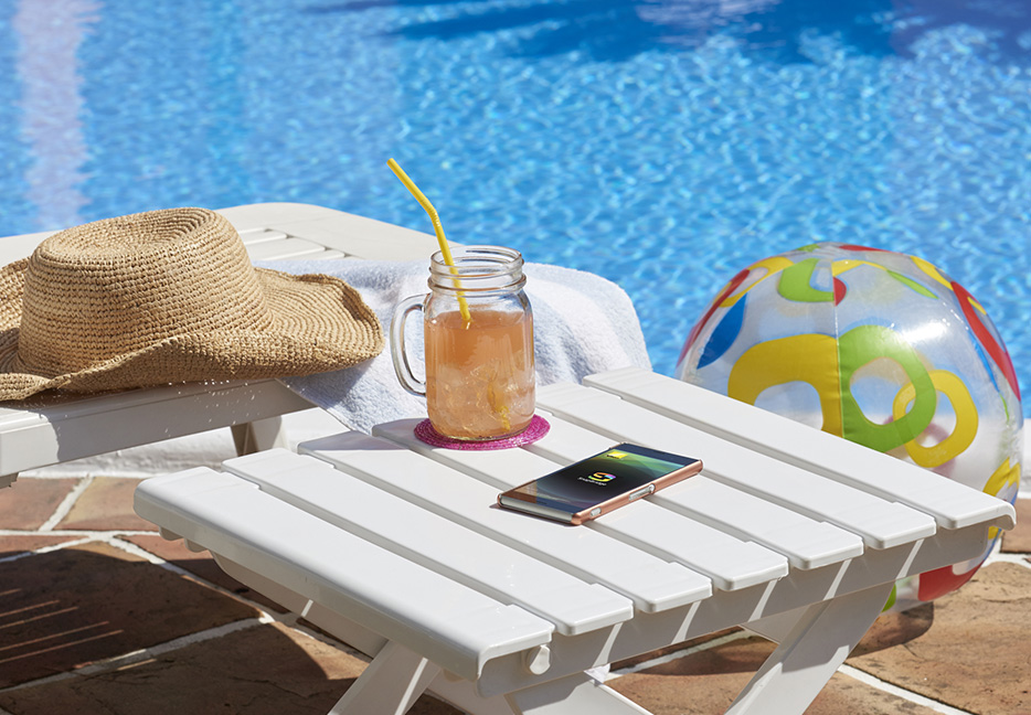 COOLPIX W100 photo of a smartphone, hat, beachball and table poolside