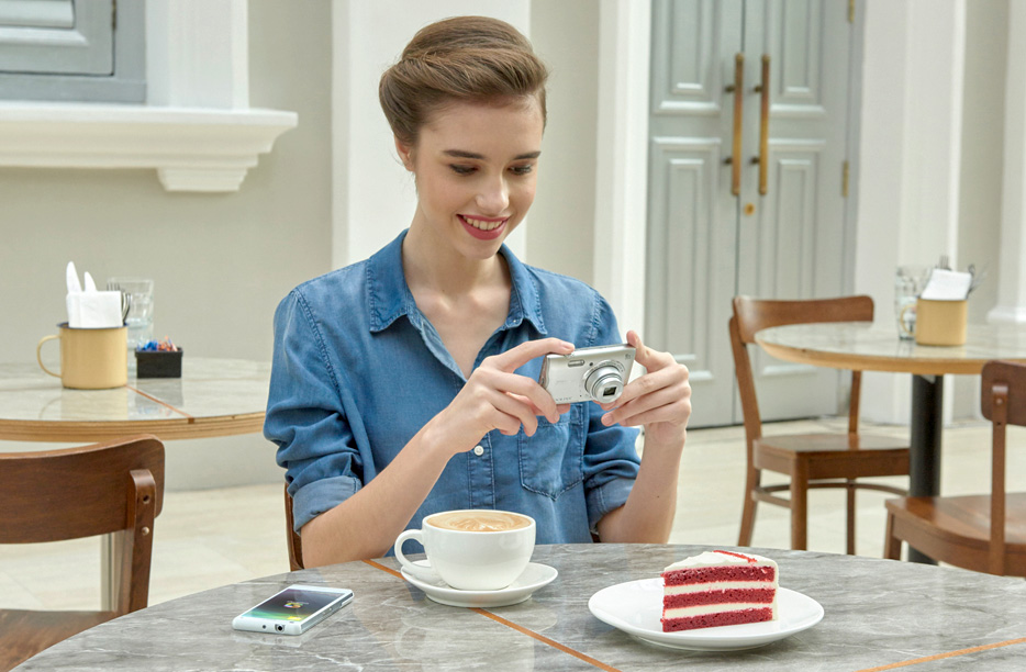 Photo of a woman at a table with cake and coffee, a smartphone and a COOLPIX A300 in her hands