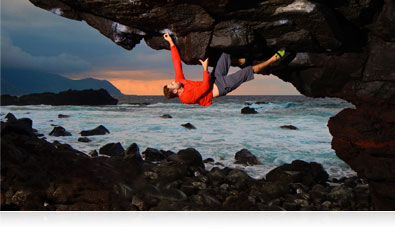 Photo of a rock climber upside down on a cliff over water highlighting the AW120's AF