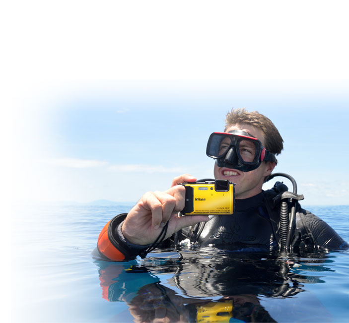 Photo of a SCUBA diver on the water's surface holding the AW130 in his hand