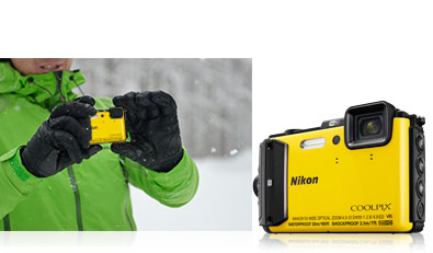 Photo of a person in a green ski jacket in the snow holding the yellow COOLPIX AW130 and the camera inset next to the photo