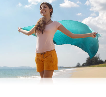 COOLPIX S33 photo of a woman holding a blue scarf in the wind behind her at the shore
